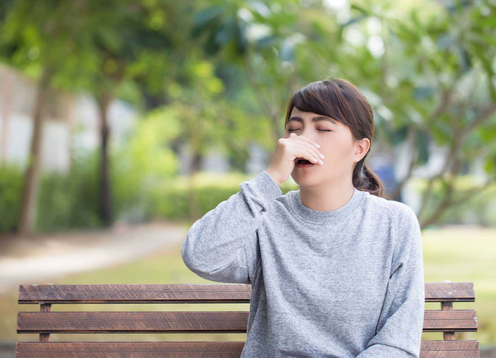 Woman sneezing from seasonal allergies